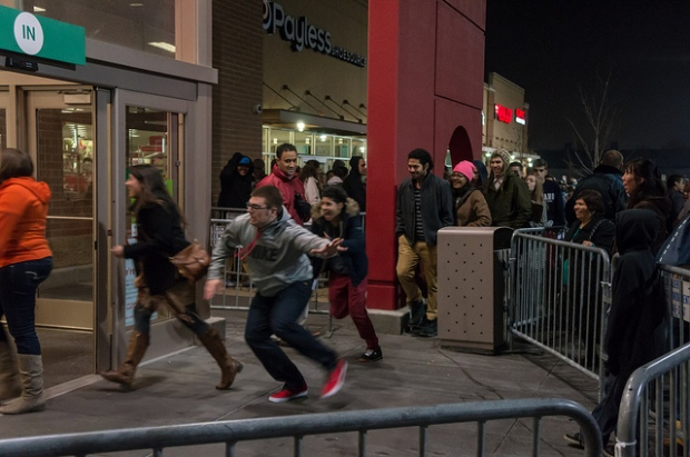 Black Friday crowds line the front of a store; customers in line rush inside